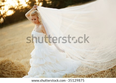 Beautiful bride posing in autumn field with veil at sunset