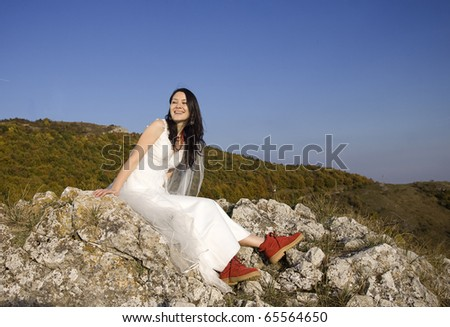Beautiful bride posing on rocks in high mountain scenery