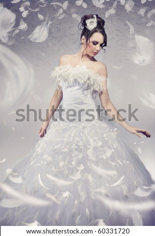 Beautiful bride posing over white flying feathers