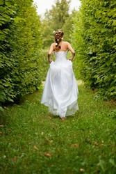 Beautiful bride running in the garden
