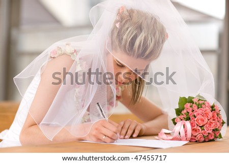 Beautiful bride sign up marriage certificate - stock photo
