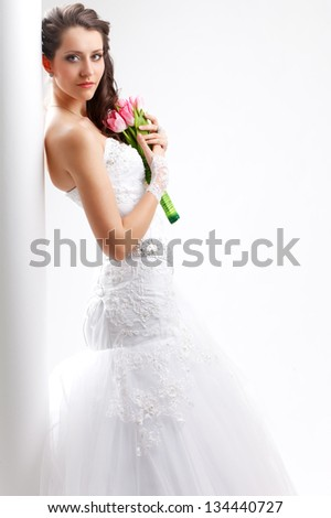 beautiful bride standing back to the  white column, studio shot