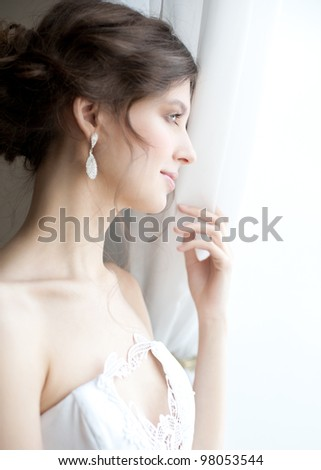 Beautiful bride standing near the window and looking away
