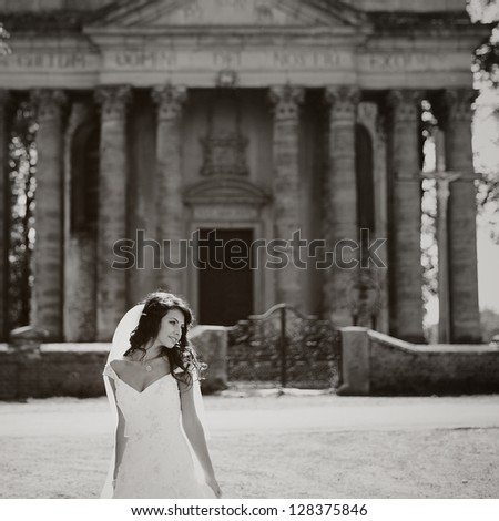 beautiful  bride stands next to old church, black and white - stock photo