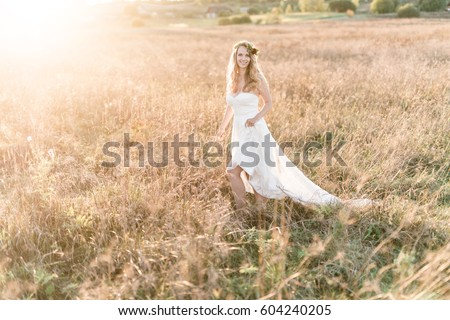 Beautiful bride wearing a natural flower wreath and standing in the golden summer fields. #604240205