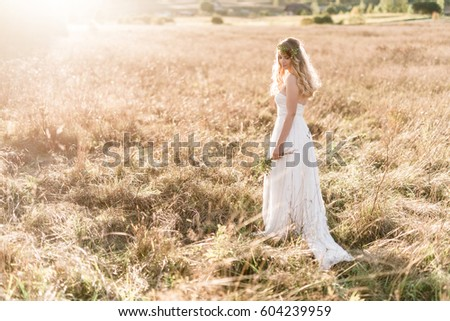 Beautiful bride wearing a natural flower wreath and standing in the golden summer fields with eucalyptus in hands. #604239959