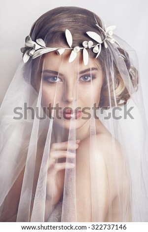 Shutterstock Beautiful bride with fashion wedding hairstyle - on white background.Closeup portrait of young gorgeous bride. Wedding. Studio shot.Beautiful bride portrait with veil over her face