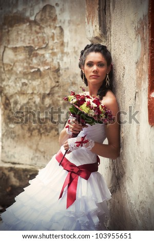 Beautiful bride with wedding bouquet in her hands leaning against the wall of an old building