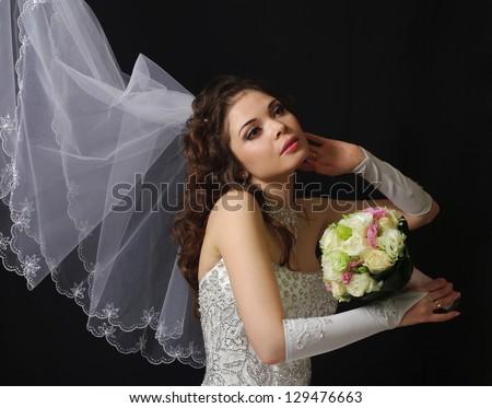Beautiful bride with wedding bouquet on a dark background