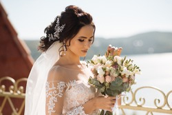 Beautiful bride with wedding flowers bouquet, attractive woman in wedding dress. Happy newlywed woman. Bride with wedding makeup and hairstyle. Smiling bride. Wedding day. Gorgeous bride. Marriage.