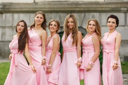 Beautiful bridesmaids in pink dresses posing and looking to camera at wedding day. Group wedding portrait of guests without bride and groom