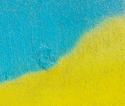 Beautiful bright colorful street art graffiti background. Abstract creative spray drawing fashion colors on the walls of the city. Ukraine flag, yellow , blue ,light texture