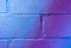Beautiful bright colorful street art graffiti background. Abstract creative spray drawing fashion colors on the brick walls of the city. Urban Culture blue , purple, neon gradient backdrop