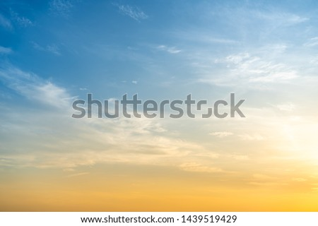 Beautiful bright orange - yellow cloudy sky during the sunrise and sunset. Beautiful scenic gradient sky between hot and cool tone of twilight sky with a cloud. Sun beam background.