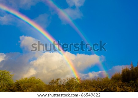 Beautiful bright rainbow in blue sky with clouds