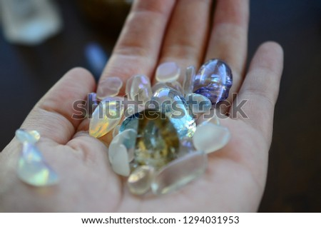 Beautiful, bright tumbled crystal chips. Stunning healing crystals. Macro photograph, low exposure. Hand holding crystals, bright healing crystals. Crisp colors and lighting, clear quartz, opalite