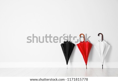 Beautiful bright umbrellas on floor near white wall with space for design #1171815778