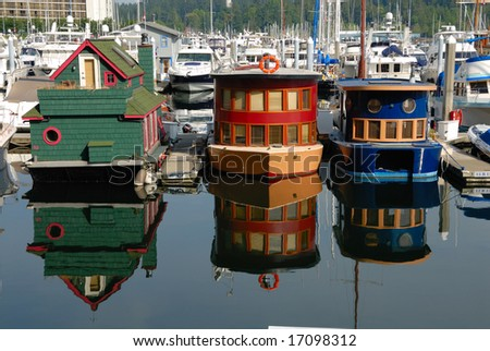 beautiful brightly painted houseboats with reflections in Vancouver marina