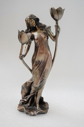 Beautiful bronze statuette of a standing girl in a beautiful dress with flowers on a white background. Candlestick.