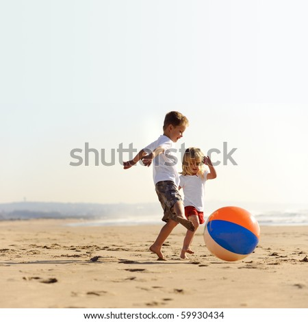 Beautiful brother and sister play with a beach ball outdoors