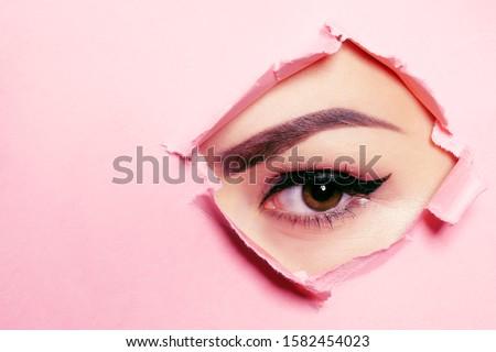 Beautiful brown eye, perfect eyebrows. Beauty salon, eyebrow master, tattoo master shooter and eyebrow. Beautiful eye on a pink background.