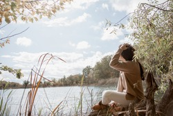 Beautiful brown hair woman in cozy  sitting on the wooden pier near lake. Woman relax and enjoy the view of fall leaves forest.