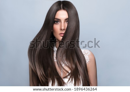 Beautiful brown-haired girl with a perfectly smooth hair, and classic make-up. Beauty face and hair. Picture taken in the studio.