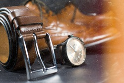 Beautiful brown leather men's shoes. Fashionable shoes isolated on black background. Focus on brown leather belt. Vintage effect.