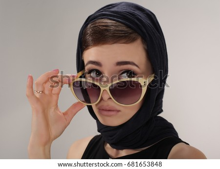 beautiful brunet woman in retro style with headscarf and sunglasses on light background