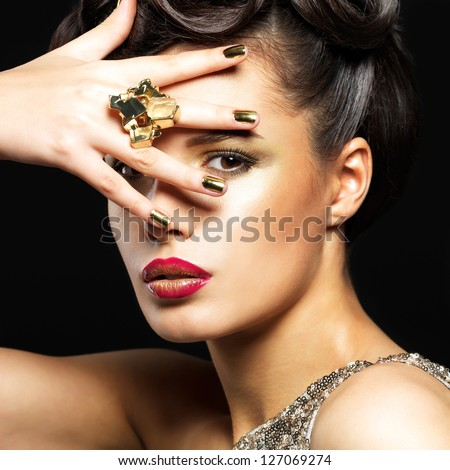 Beautiful brunet woman with golden nails and style makeup of eyes -  on black background
