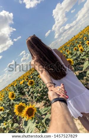 Beautiful brunett girl in white dress hand in hand with husband going to sunflowers field. #1457527829
