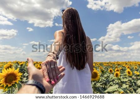 Beautiful brunett girl in white dress hand in hand with husband going to sunflowers field. #1466929688