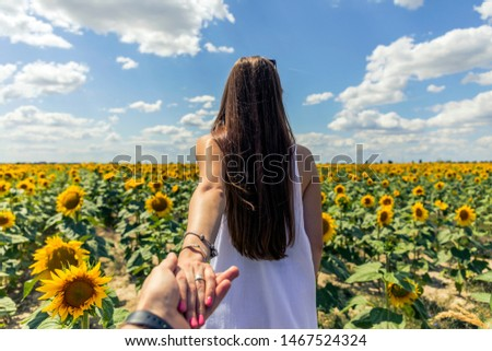 Beautiful brunett girl in white dress hand in hand with husband going to sunflowers field. #1467524324