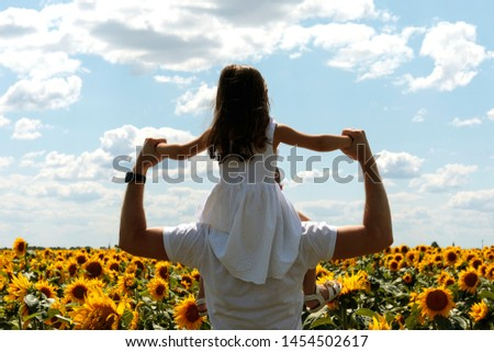 Beautiful brunett girl in white dress in her father's neck going to sunflowers field. Father and daughter concept. #1454502617