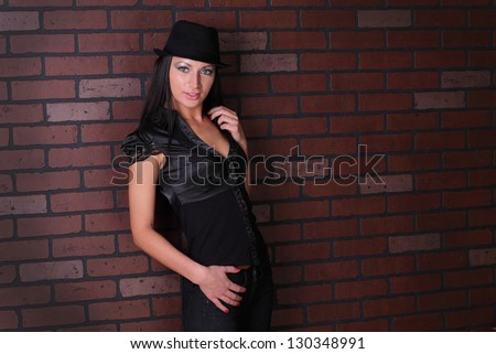 beautiful brunette against the wall in a shirt and a hat #130348991