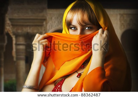 Beautiful brunette asian girl eyes. Arab Woman with orange and yellow veil on face, traditional east costume