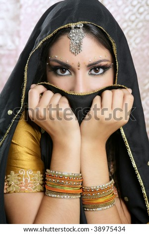 Beautiful brunette asian girl with black veil on face, traditional indian costume