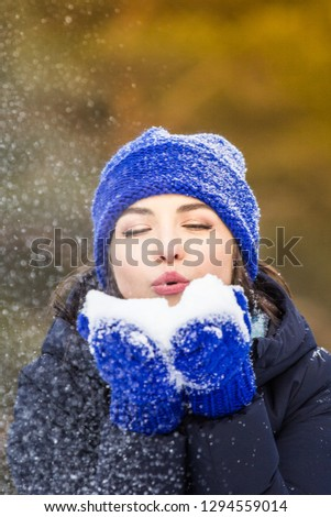 beautiful brunette blows snow from her palms