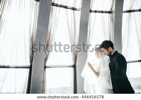 Beautiful brunette bride and bridegroom standing close to each other at big window at background, wedding photo, copy space. #446456578