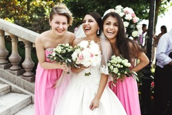 Beautiful brunette bride and gorgeous bridesmaids with bouquets posing near stairs