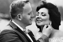 Beautiful brunette bride kissing handsome groom lake background closeup b&w