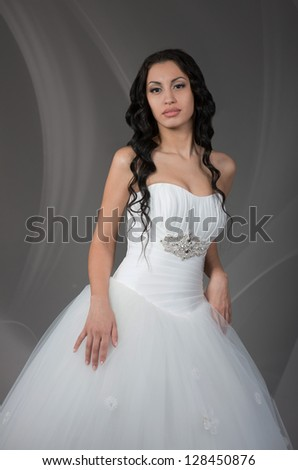 Beautiful brunette bride posing for photo, on grey background