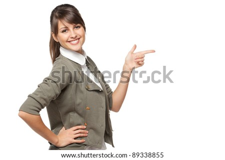 Beautiful brunette business woman pointing at copy space over white background