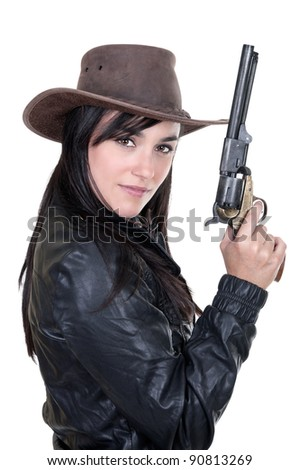 Beautiful brunette cowgirl model holding a gun, isolated on white