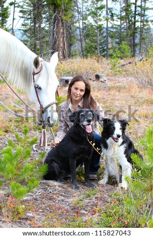 Beautiful brunette cowgirl with her horse and dogs