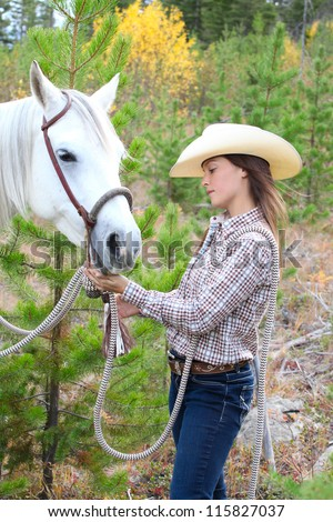 Beautiful brunette cowgirl with her horse on a mountain trail ride