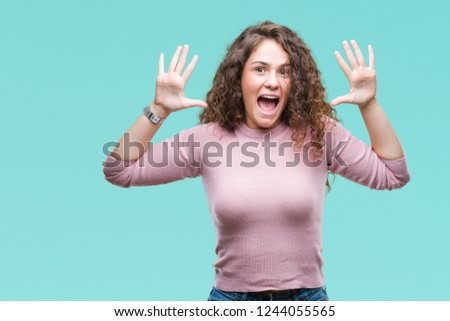 Beautiful brunette curly hair young girl wearing pink sweater over isolated background showing and pointing up with fingers number ten while smiling confident and happy. #1244055565