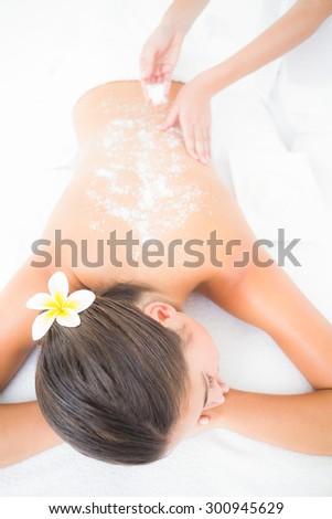 Beautiful brunette enjoying a salt scrub treatment at the health spa