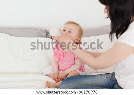 Beautiful brunette female bottle-feeding her baby on a bed in her apartment