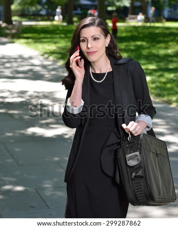 Beautiful brunette female  business woman walks in city park - carrying brief case over arm and talking on cell phone